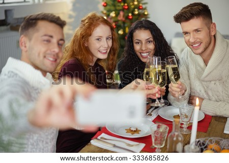 friends taking a selfie while having christmas dinner at home - stock photo