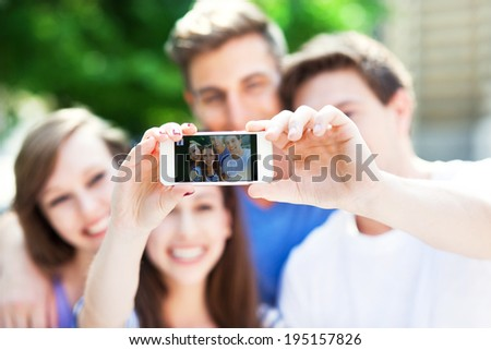 Friends taking photo of themselves   - stock photo