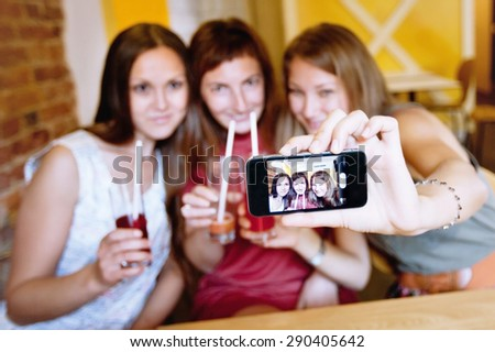 friends taking photo of themselves in cafe during party - stock photo