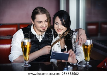 Friends taking picture of themselves with smartphone, couple in love