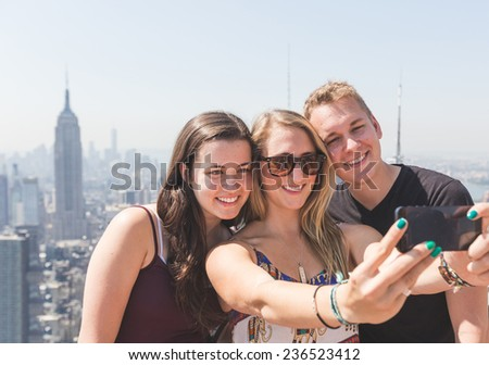 Friends Taking Selfie with New York on Background - stock photo