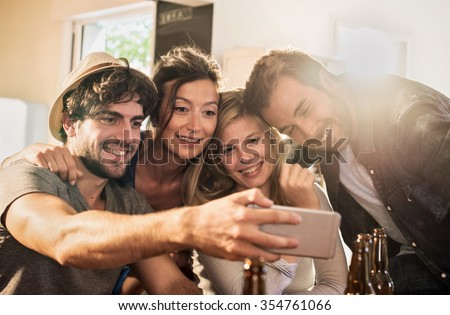 Friends taking selfies on a smartphone in a charming house. Two men and two women are holding each other arms in arms while the phone is taking the picture. Backlit shot with flare, real people. - stock photo