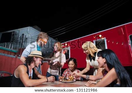 Friends talking and eating pizza near Food Truck - stock photo