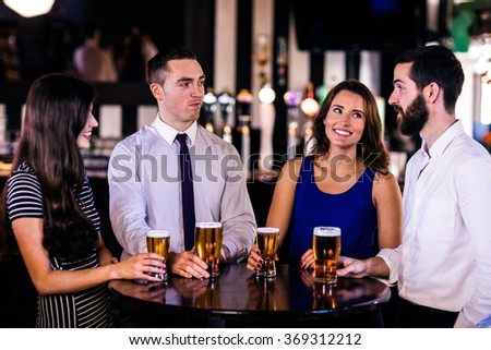 Friends talking and having a beer in a bar