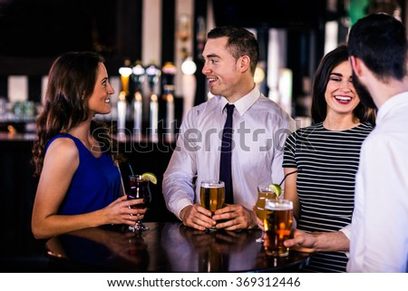 Friends talking and having a drink in a bar
