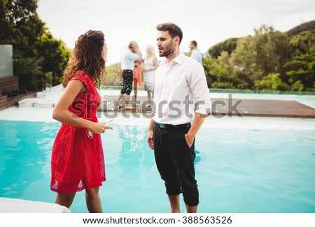 Friends talking near pool while other group of friends standing at distance - stock photo