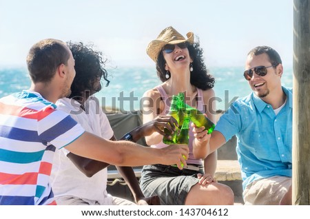 Friends toasting drinks at the beach party on a sunny afternoon, having fun on holiday - stock photo