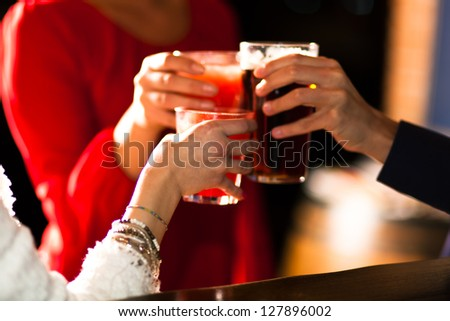 Friends toasting glasses in a pub - stock photo