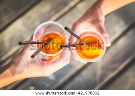 Friends toasting with drinks. The main subject are two hands holding glasses with cocktail inside. The drink is orange with a slice of orange inside and two black straws.