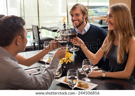 Friends toasting with glasses of red wine in a restaurant - stock photo