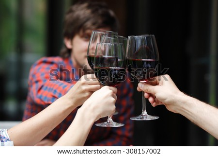 friends toasting with wine at dinner - stock photo