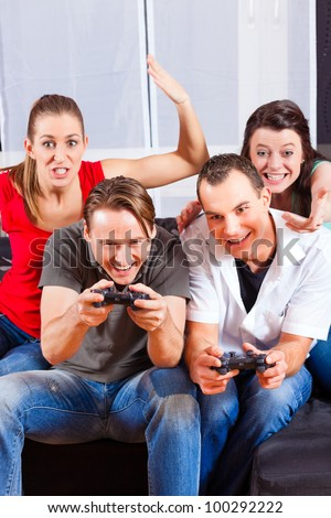 Friends - two couples - sitting in front of game console box and do have lots of fun - stock photo