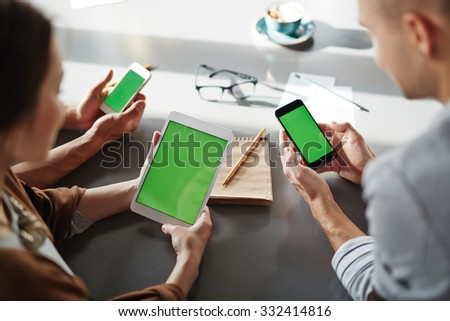 Friends using different devices in cafe - stock photo