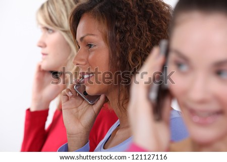 Friends using mobile telephones - stock photo
