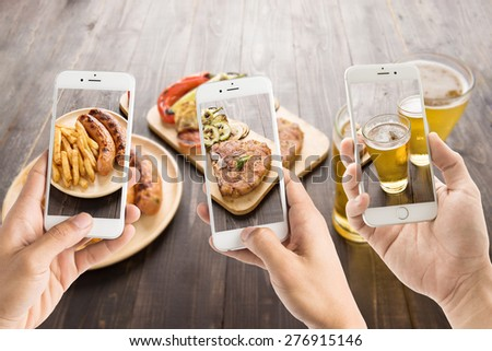 friends using smartphones to take photos of sausage and pork chop and beer. - stock photo