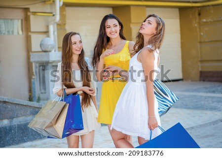 Friends walk together. Girls holding shopping bags and walk to the shops. Beautiful girl dressed in dresses
