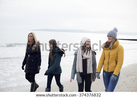 Friends walking along a Beach having fun - stock photo