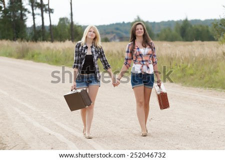 Friends walking and holding hands in ciuntryside - stock photo