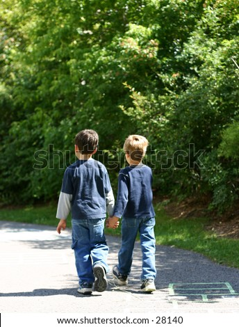 Friends walking away from us on a path - stock photo
