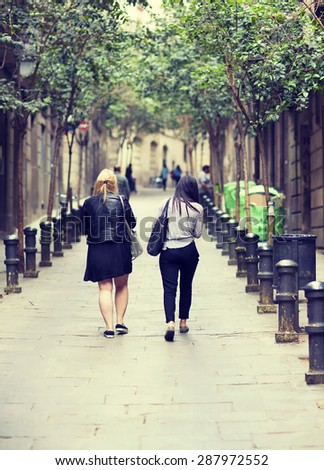 Friends walking in the streets and shopping with bags on their shoulder. Image has a vintage effect.