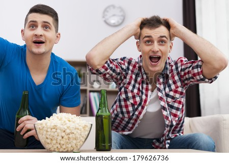 Friends watching sports on TV - stock photo
