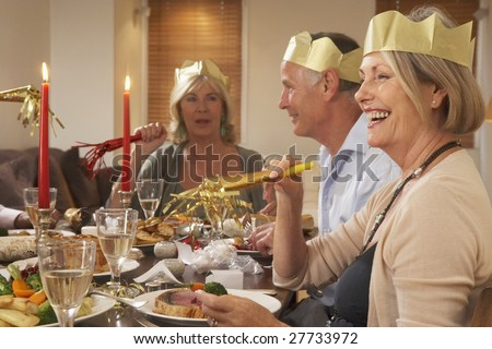 Friends Wearing Party Hats At A Dinner Party