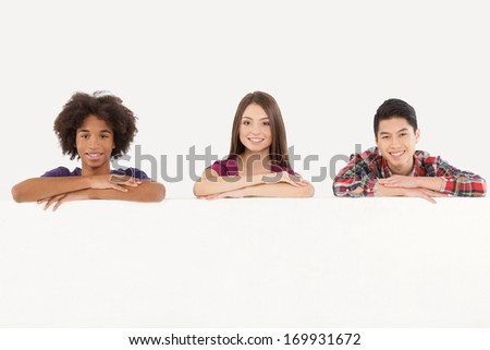 Friends with copy space. Cheerful young multi-ethnic people leaning at copy space and smiling at camera while isolated on white - stock photo