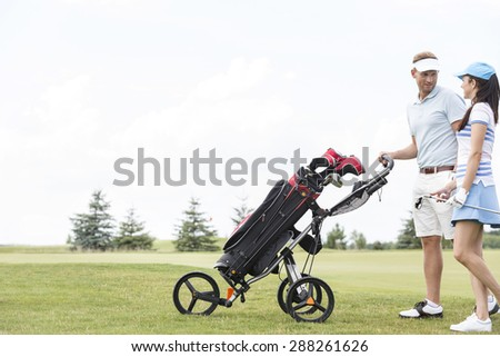 Friends with equipment talking while walking at golf course against clear sky - stock photo