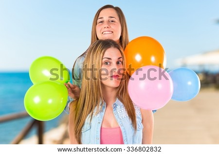 Friends with many balloons over unfocused background