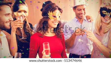 Friends with masks on holding champagne flute against flying colours