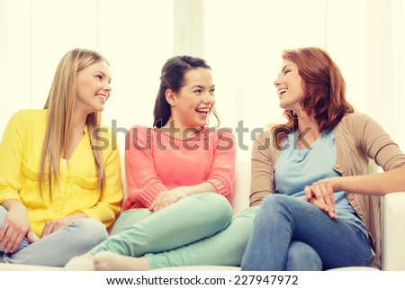 friendship and happiness concept - three girlfriends having a talk at home - stock photo