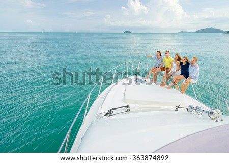 Friendship and happy young people standing on the yacht deck looking and pointing away sailing the sea. - stock photo