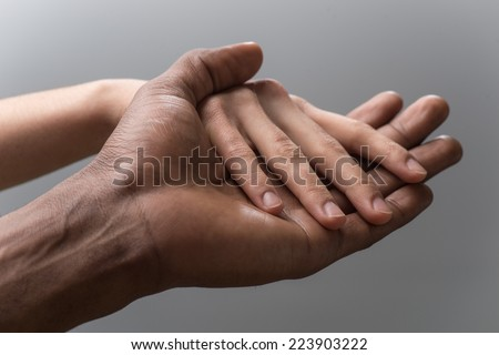 Friendship and love concept between man and woman. man's hand hold by girl hand isolated on grey background  - stock photo