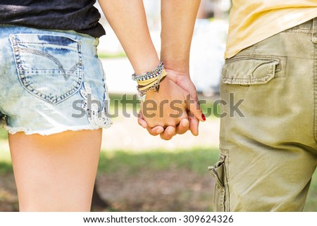 Friendship and love of man and woman - girl and guy hand in hand walking away in nature park - backside of two young guys in love - concept of romantic moment on honeymoon - summer outfit clothes - stock photo