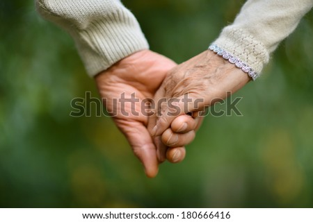Friendship and love of man and woman: two hands over nature - stock photo