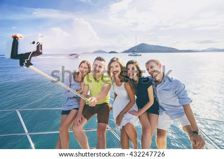 Friendship and vacation. Group of young handsome men and women taking selfie together on the yacht sailing the sea. - stock photo