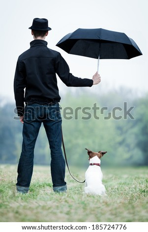 friendship between dog and owner standing in the rain with umbrella - stock photo