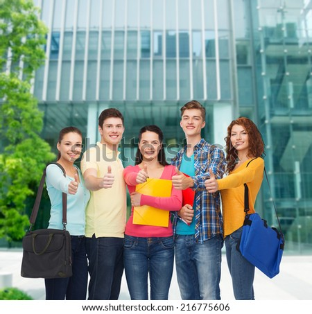 friendship, business, education and people concept - group of smiling teenagers with folders and school bags showing thumbs up over campus background - stock photo