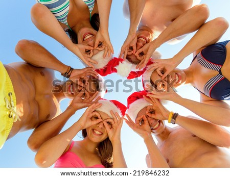 friendship, christmas, summer vacation, holidays and people concept - group of smiling friends wearing swimwear and santa helper hats standing and having fun in circle over blue sky - stock photo