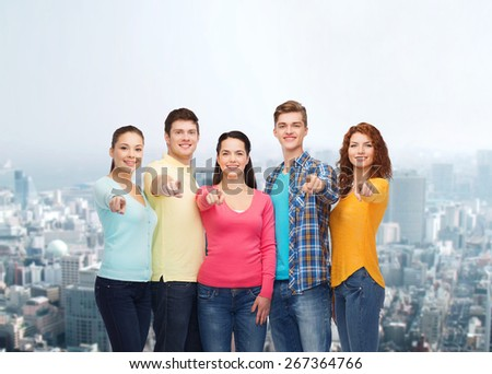 friendship, city life and people concept - group of smiling teenagers over city background - stock photo