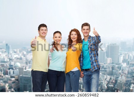 friendship, city life and people concept - group of smiling teenagers showing thumbs up over city background - stock photo