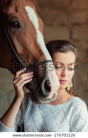 Friendship. Close up portrait of young beautiful woman with brown horse.