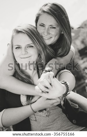 Friendship concept. Black and white portrait of two happy smiling girls hug over sky outdoors background - stock photo