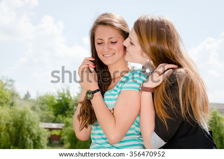 Friendship concept. Two smiling girls whispering gossip - stock photo