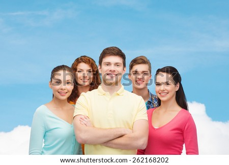 friendship, dream and people concept - group of smiling teenagers standing over blue sky with white cloud background