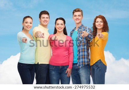friendship, dream, future and people concept - group of smiling teenagers pointing fingers on you over blue sky with white cloud background - stock photo