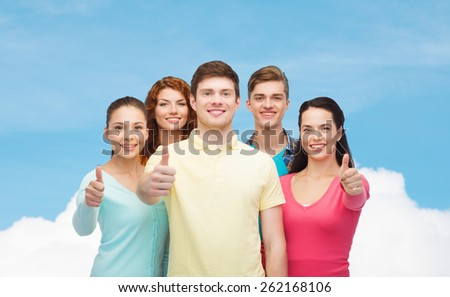friendship, dream, future and people concept - group of smiling teenagers showing thumbs up over blue sky with white cloud background - stock photo