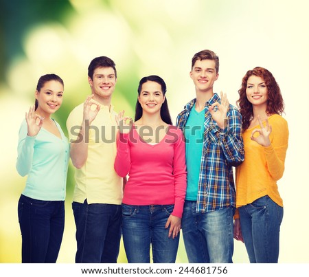 friendship, ecology, gesture and people concept - group of smiling teenagers showing ok sign over green background - stock photo