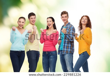 friendship, ecology, nature, teamwork and people concept - group of smiling teenagers showing triumph gesture over green background - stock photo