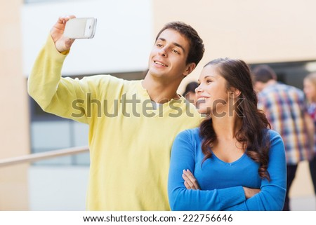friendship, education and people concept - group of smiling students making selfie with smartphone outdoors - stock photo